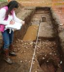 Janey Green draws a cobbled feature in Trench 6